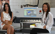 Elena and Olga Konopleva, Managing Directors of Duprint,in front of their POLAR N 92 PRO Product samples - laminated catalog covers